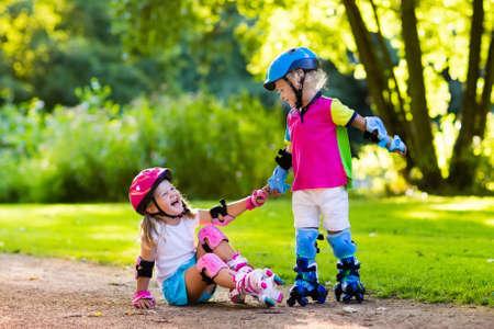 Niña y niño a aprender a patinar en el parque de verano. Los niños llevaban almohadillas de protección y casco de seguridad para una conducción segura de patinaje sobre ruedas. deporte al aire libre para los niños activos. Los hermanos ayudan y se apoyan mutuamente