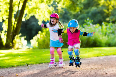 blades: Girl and boy learn to roller skate in summer park. Children wearing protection pads and safety helmet for safe roller skating ride. Active outdoor sport for kids. Siblings help and support each other