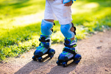 elbow pads: Little boy learning to roller skate in summer park. Children wearing protection pads for safe roller skating ride. Active outdoor sport for kids. Close up view of skates.