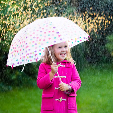 Little girl playing in rainy summer park. Child with colorful rainbow umbrella, pink coat walking in the rain. Kid having fun in autumn shower. Outdoor activity by any weather