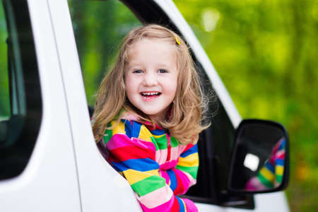 road safety: Little girl with funny pigtails watching out of car window sitting on front driver seat during a break on a family vacation road trip on summer day. Child in white minivan. Traveling by car with kids.