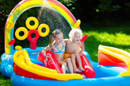 garden center: Children playing in inflatable baby pool. Kids swim and splash in colorful garden play center. Happy boy and girl playing with water toys on hot summer day. Family having fun outdoors in the backyard. Stock Photo