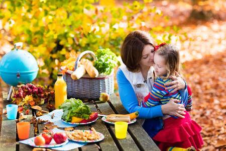 comiendo frutas: Madre joven feliz con la niña asar la carne y hacer sándwich y ensalada en una mesa de picnic en el parque soleado de otoño. diversión barbacoa para los padres con niños en el día caliente de la caída. Parrilla y fiesta de barbacoa. Foto de archivo
