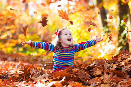Happy little girl playing in beautiful autumn park on warm sunny fall day. Kids play with golden maple leaves. Standard-Bild