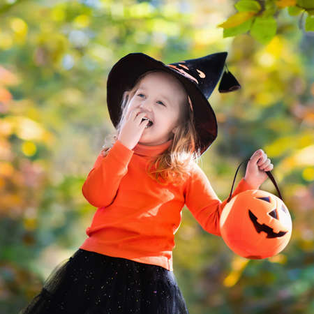 treating: Little girl in witch costume playing in autumn park. Child having fun at Halloween trick or treat. Kids trick or treating. Toddler kid with jack-o-lantern. Children with candy bucket in fall forest.
