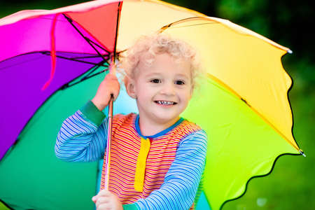 rain weather: Little boy playing in rainy summer park. Child with colorful rainbow umbrella standing in the rain. Kid walking in autumn shower. Outdoor fun by any weather