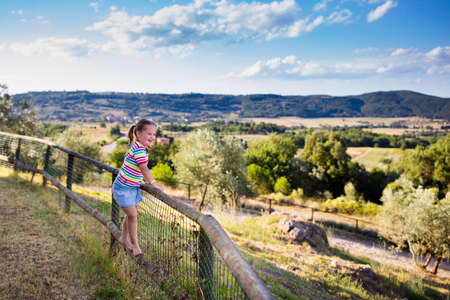 agriturismo: Happy little girl enjoying beautiful valley and mountains view of Tuscany landscape during summer vacation in Italy. Child playing on villa terrace during Italian holiday. Family traveling in Toscana