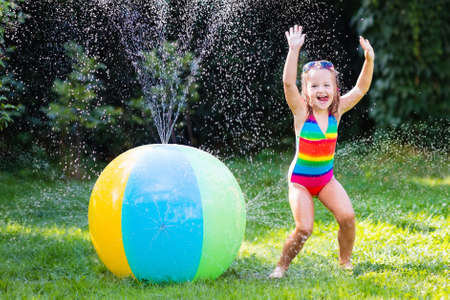 Funny laughing little girl in a colorful swimming suit playing with toy ball garden sprinkler with water splashes having fun in the backyard on a sunny hot summer vacation day Stock Photo