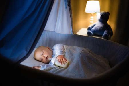 かわいい赤ちゃんが夜天蓋付き青バシネットで牛乳を飲みます。ベビーベッド、ランプ、おもちゃのクマと暗い部屋で寝る準備式のボトルとパジャ