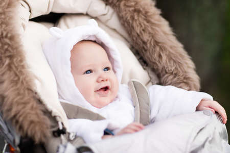 Happy laughing baby enjoying a walk in winter park sitting in a warm stroller with sheepskin hood