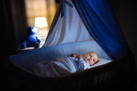 bassinet: Adorable baby sleeping in blue bassinet with canopy at night. Little boy in pajamas taking a nap in dark room with crib, lamp and toy bear. Bed time for kids. Bedroom and nursery interior. Stock Photo