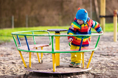 school yard: Little boy on a playground. Child playing outdoors in autumn. Kids play on school yard. Happy kid in kindergarten or preschool. Children having fun at daycare play ground. Toddler on a swing. Stock Photo