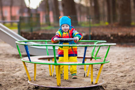 Little boy on a playground. Child playing outdoors in autumn. Kids play on school yard. Happy kid in kindergarten or preschool. Children having fun at daycare play ground. Toddler on a swing. Stock Photo