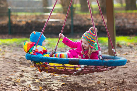 kids having fun: Little boy and girl on a playground. Child playing outdoors in autumn. Kids play on school yard. Happy kid in kindergarten or preschool. Children having fun on cold fall day. Toddler on a swing.