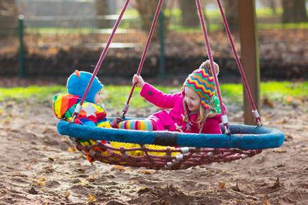 niñas gemelas: Niño pequeño y muchacha en un patio. Niño que juega al aire libre en otoño. Los niños juegan en el patio de la escuela. niño feliz en la guardería o al preescolar. Los niños que se divierten en un día frío de la caída. Niño en un columpio. Foto de archivo