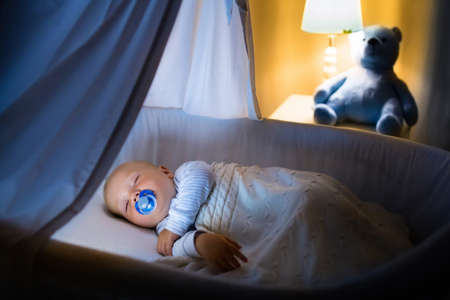 taking nap: Adorable baby with pacifier sleeping in blue bassinet with canopy at night. Little boy in pajamas taking a nap in dark room with crib, lamp and toy bear. Bed time for kids. Bedroom and nursery interior.