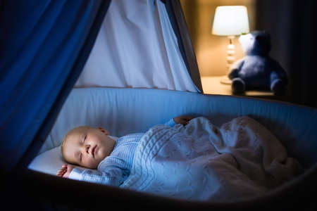 asleep: Adorable baby sleeping in blue bassinet with canopy at night. Little boy in pajamas taking a nap in dark room with crib, lamp and toy bear. Bed time for kids. Bedroom and nursery interior. Stock Photo