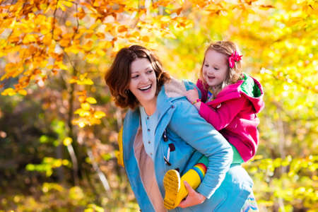 warm clothing: Mother and daughter play in autumn park. Parent and child walk in the forest on a sunny fall day. Children playing outdoors with yellow maple leaf. Toddler girl picking golden leaves. Mom hugging kid. Stock Photo
