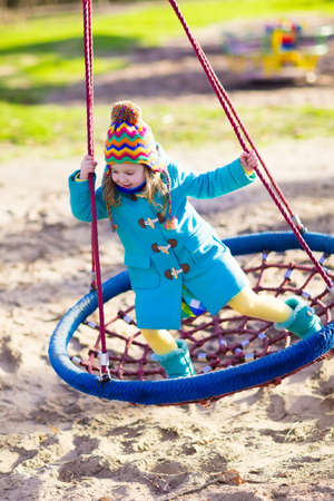 Little girl in warm coat and hat on a playground. Child playing outdoors in autumn. Kids play on school yard. Happy kid in kindergarten or preschool. Children having fun on cold fall day. Toddler on a swing. Stock Photo