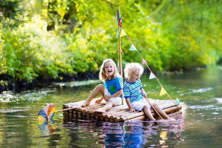 Dvě děti na dřevěný vor chytání ryb s barevnými sítí v řece a hrát si s vodou na horkém letním dni. Venkovní zábavu a dobrodružství pro děti. Chlapec a dívka v hračka člunu. Sailor role hra.