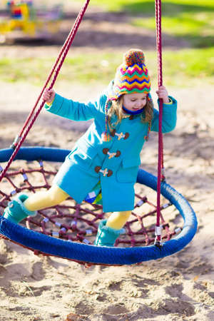 school yard: Little girl in warm coat and hat on a playground. Child playing outdoors in autumn. Kids play on school yard. Happy kid in kindergarten or preschool. Children having fun on cold fall day. Toddler on a swing. Stock Photo