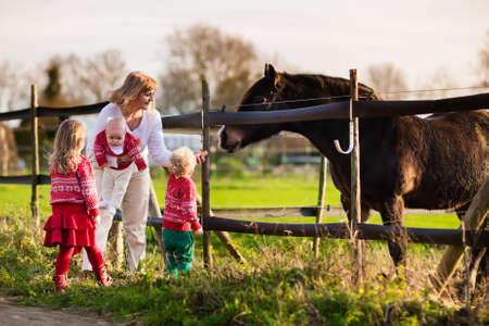 Familie op een boerderij in de herfst. Moeder en kinderen te voeden van een paard. Outdoor plezier voor ouders en kinderen. Vrouw met baby en peuter spelen met huisdieren. Kind voeden dier op een ranch op koude herfstdag.