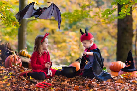 pitchfork: Two funny kids wearing devil and vampire costume with red horns and trident trick or treating on Halloween. Children dressed up as witch play in autumn park. Stock Photo