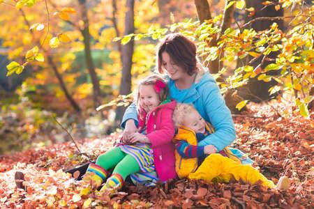 botas de lluvia: La madre y los niños juegan en el parque de otoño. Los padres y los niños caminan en el bosque en un día soleado de otoño. Niños y niñas jugando al aire libre con la hoja de arce de color amarillo. Niño recogiendo las hojas de oro. Madre abrazando niño. Foto de archivo