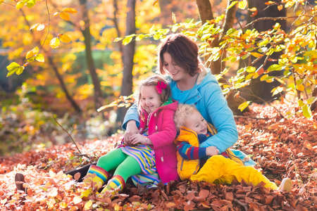 rain boots: Mother and kids play in autumn park. Parent and children walk in the forest on a sunny fall day. Boy and girl playing outdoors with yellow maple leaf. Toddler picking golden leaves. Mom hugging kid.