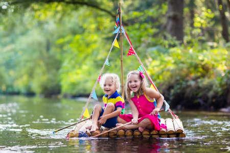 나무 뗏목이 강에서 다채로운 그물로 물고기를 잡는 뜨거운 여름 날에 물 재생에 두 아이. 야외 재미와 아이들을위한 모험. 장난감 보트에서 소년과 소
