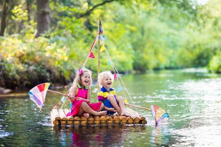 Twee kinderen die op houten vlot het vangen van vis met een kleurrijk net in een rivier en het spelen met water op hete zomerdag. Outdoor plezier en avontuur voor kinderen. Jongen en meisje in speelgoed boot. Sailor rol spel.