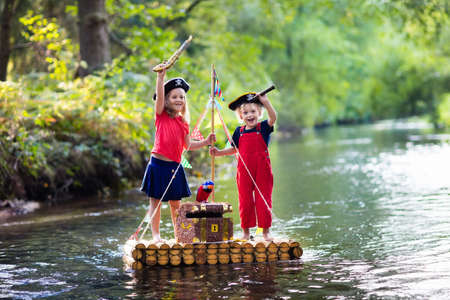 Kids dressed in pirate costumes and hats with treasure chest, spyglasses, and swords playing on wooden raft sailing in a river on hot summer day. Pirates role game for children. Water fun for family.