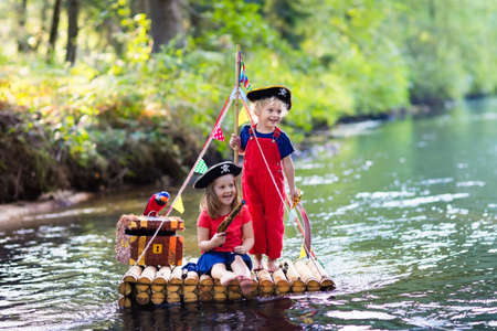 cutlass: Kids dressed in pirate costumes and hats with treasure chest, spyglasses, and swords playing on wooden raft sailing in a river on hot summer day. Pirates role game for children. Water fun for family. Stock Photo