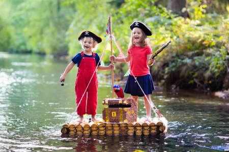 해적 의상과 보물 상자, spyglasses와 모자를 입고 아이, 그리고 뜨거운 여름 날에 강에 나무 뗏목 항해에서 재생 칼입니다. 어린이를위한 해적 역할 게임.
