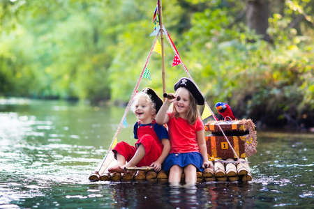Kids dressed in pirate costumes and hats with treasure chest, spyglasses, and swords playing on wooden raft sailing in a river on hot summer day. Pirates role game for children. Water fun for family. Banco de Imagens