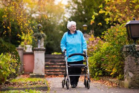 empujando: Señora feliz minusválidos mayor con una discapacidad para caminar disfrutando de un paseo en un parque otoño empujando su andador o silla de ruedas. Ayuda y soporte durante la jubilación. Paciente de hogar de ancianos o centro de atención. Foto de archivo