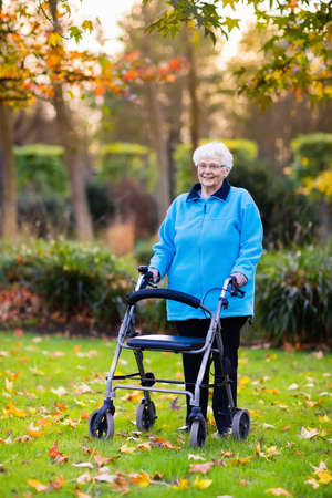 great grandmother: Happy senior handicapped lady with a walking disability enjoying a walk in an autumn park pushing her walker or wheel chair. Aid and support during retirement. Patient of nursing home or care center.