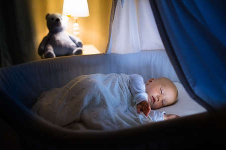 Adorable bebé durmiendo en la cuna azul con dosel en la noche. El niño pequeño en pijama tomando una siesta en una habitación oscura con el pesebre, la lámpara y el juguete. la hora de dormir para los niños. Dormitorio y cuarto de niños interior.