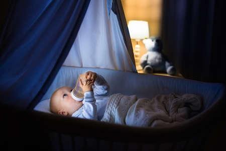 Schattige baby het drinken van melk in blauwe mandewieg met luifel 's nachts. Kleine jongen in pyjama met formule fles klaar om te slapen in een donkere kamer met een wieg, lamp en speelgoed beer. Bedtijd drank voor kinderen.