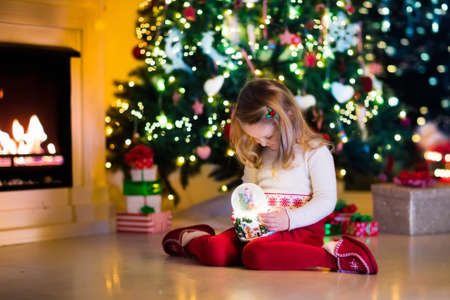 christmas tree presents: Family on Christmas eve at fireplace. Little girl opening Xmas presents holding snow globe. Child under Christmas tree with gift boxes. Decorated living room. Cozy winter evening at home.