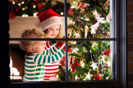 少しの幸せが一致する赤で子供し、緑の縞模様のパジャマは、伝統的な暖炉付きの美しいリビング ルームでクリスマス ツリーを飾る。クリスマスイ