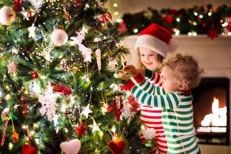 Niños felices con pijamas a rayas rojas y verdes a juego decoran el árbol de Navidad en la hermosa sala de estar con chimenea tradicional. Niños abriendo regalos en la víspera de Navidad.