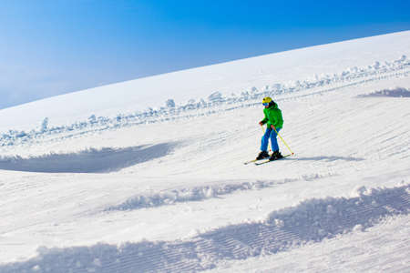 slopes: Child skiing in mountains. Active teenager kid with safety helmet, goggles and poles. Ski race for young children. Winter sport for family. Kids ski lesson in alpine school. Young skier racing in snow Stock Photo