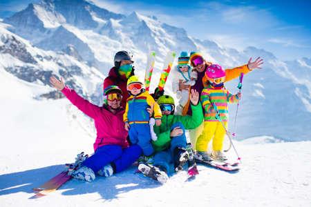 Familjeski semester. Grupp skidåkare i schweiziska Alperna bergen. Vuxna och småbarn, tonårs- och barnskidåkning på vintern. Föräldrar lär barnen alpin utförsåkning. Skidutrustningar och slitage, säkra hjälmar. Stockfoto