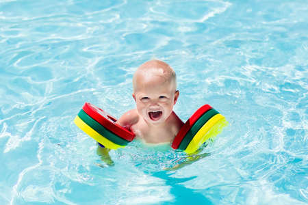 armbands: Happy laughing baby boy playing in outdoor swimming pool on a hot summer day. Kids learn to swim. Child with colorful armbands. Family vacation in tropical resort.