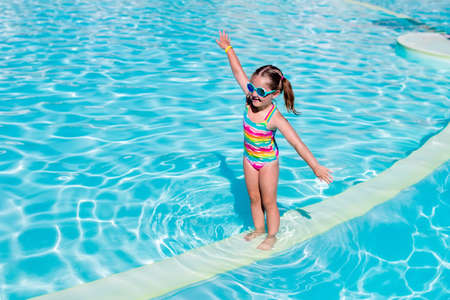 armbands: Happy laughing little girl playing in outdoor swimming pool on a hot summer day. Kid in colorful bathing suit and goggles learning to swim in tropical resort. Water fun for children. Stock Photo