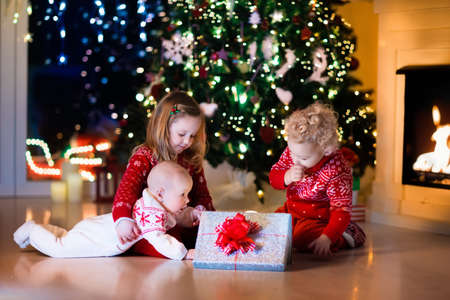 christmas tree presents: Family on Christmas eve at fireplace. Kids opening Xmas presents. Children under Christmas tree with gift boxes. Decorated living room with traditional fire place. Cozy warm winter evening at home. Stock Photo