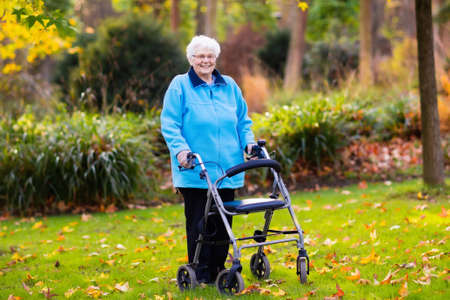 cane chair: Happy senior handicapped lady with a walking disability enjoying a walk in an autumn park pushing her walker or wheel chair. Aid and support during retirement. Patient of nursing home or care center.