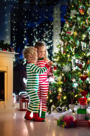 decorating: Happy little kids in matching red and green striped pajamas decorate Christmas tree in beautiful living room with traditional fire place. Children opening presents on Xmas eve.