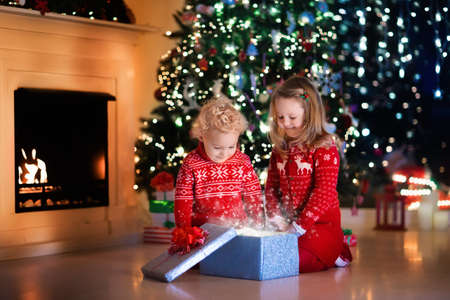 under fire: Family on Christmas eve at fireplace. Kids opening Xmas presents. Children under Christmas tree with gift boxes. Decorated living room with traditional fire place. Cozy warm winter evening at home. Foto de archivo